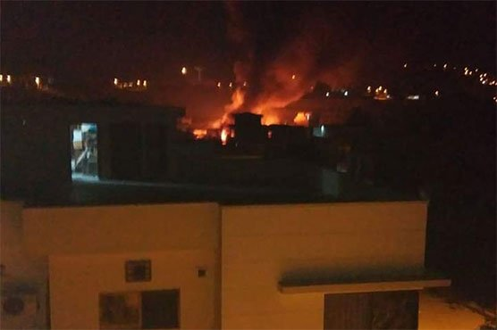 Picture showing the houses engulfed in flames after the Pakistan Army Aviation Aircraft crash landed on 5 residential houses.