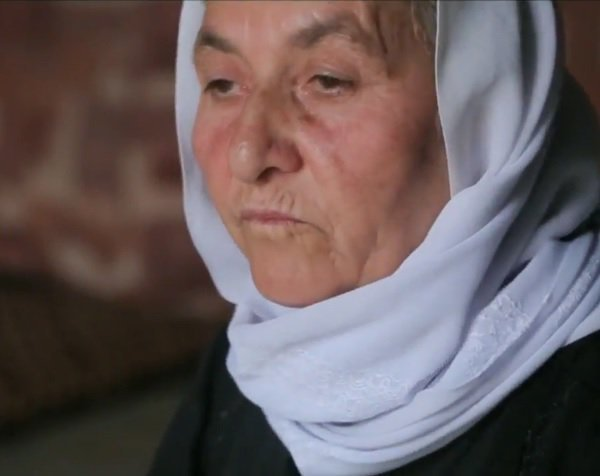 A Yazidi Old woman with pain in her eyes