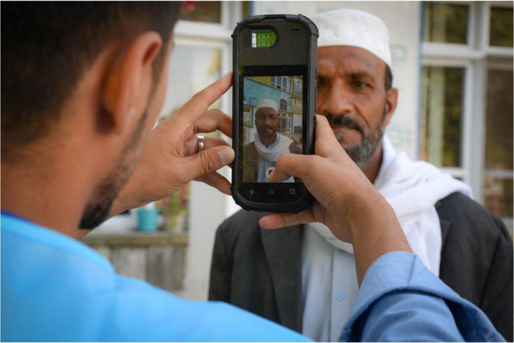 Afghan Election 2019:  An election worker checks a prospective voter, Mohammed Bashir, 54, using a biometric scanner during Afghanistan's presidential elections 28-Septeber 2019.