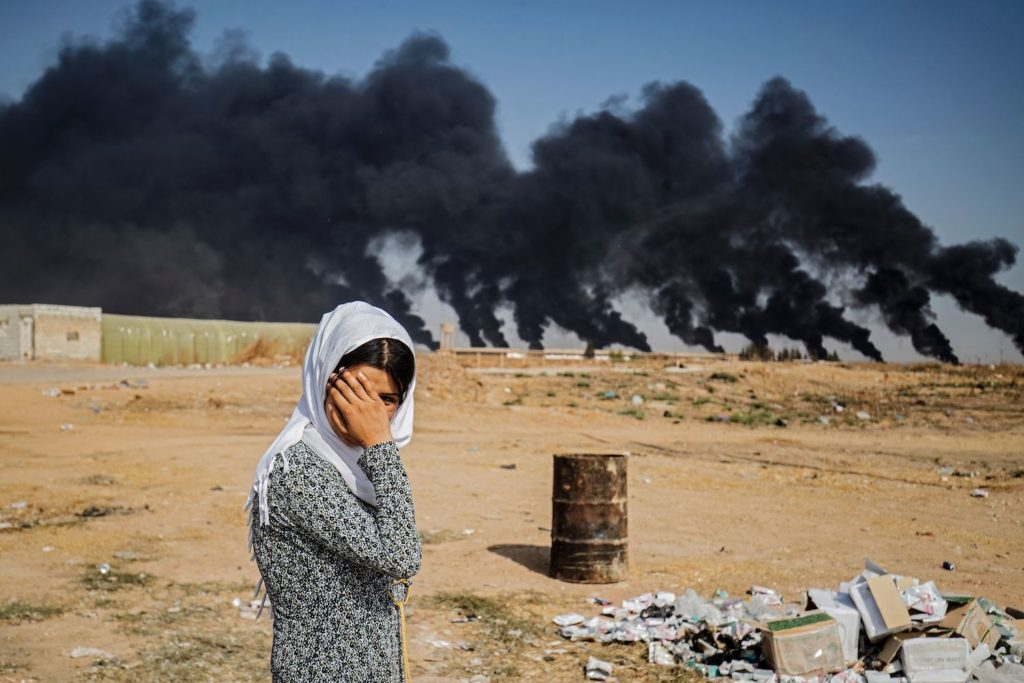 Turkey Committing War Crimes: A woman along the side of a road on the outskirts of the town of Tal Tamr near the Syrian Kurdish town of Ras al-Ain along the border with Turkey in the northeastern Hassakeh province on October 16, 2019 (Photo by DELIL SOULEIMAN/AFP via Getty Images)