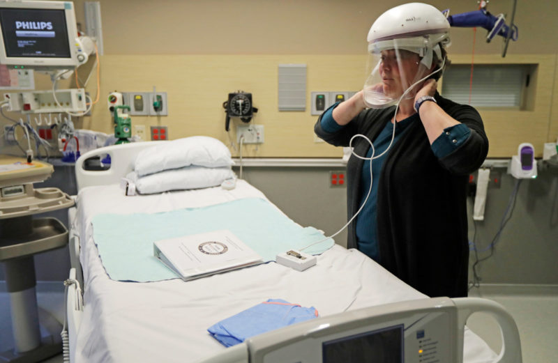 U.S. Health Care System : A nurse demonstrates how she wears a respirator helmet with a face shield intended to prevent infection.